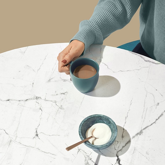 woman sits at table with coffee cup